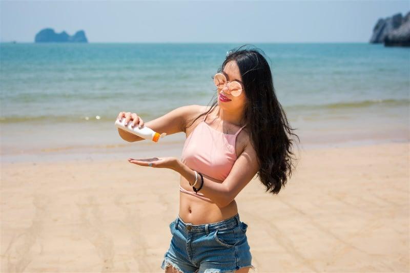 passando protetor na praia