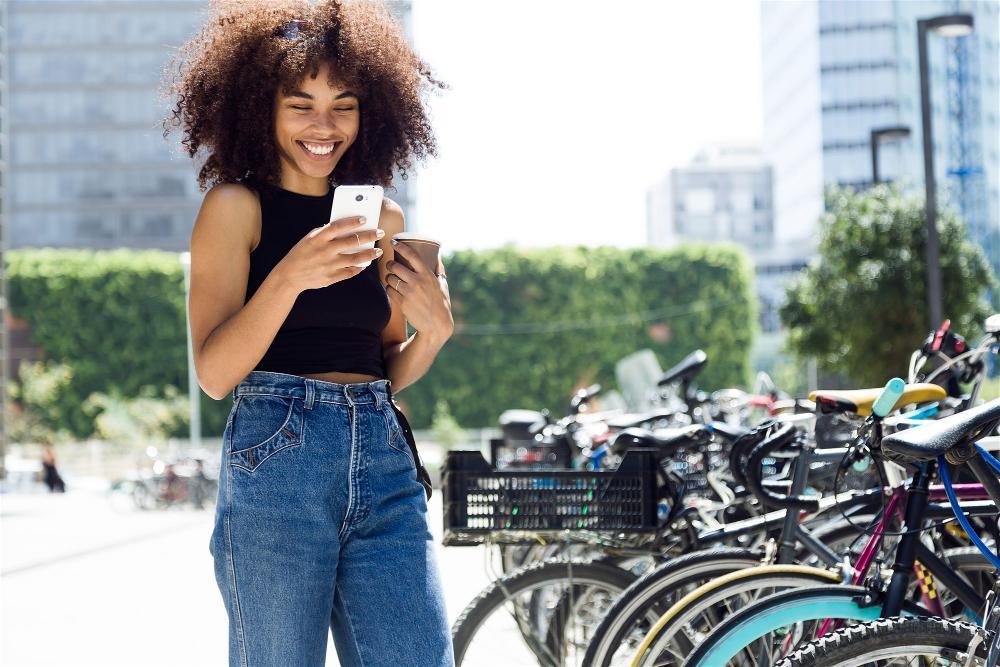 Mulher Morena bonita sorrindo e interagindo com celular