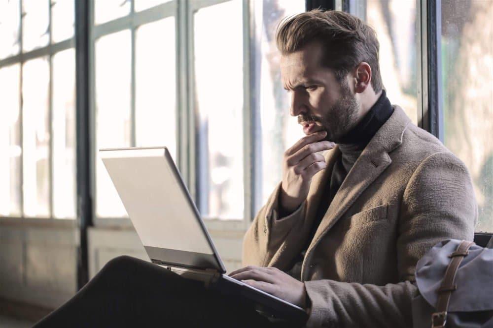 Homem pensativo, sentado com notebook sobre as pernas e olhando para a tela do mesmo