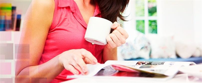 Mulher tomando café e folhando um livro