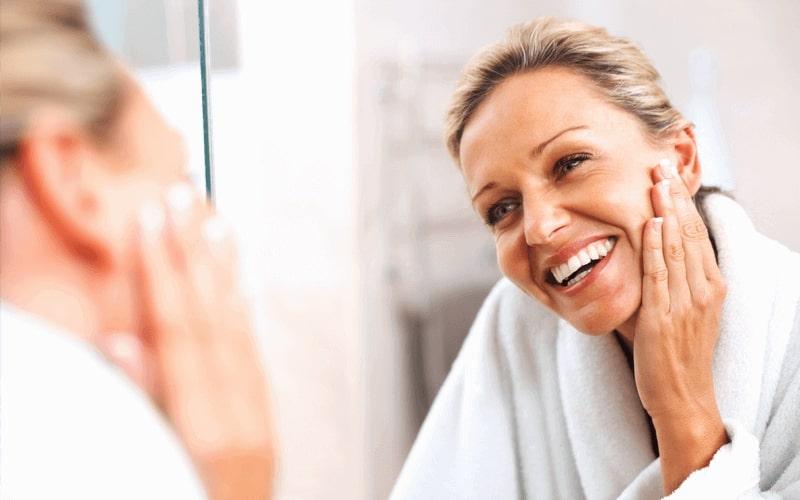 Senhora sorridente olhando para o espelhando, admirando seu rosto