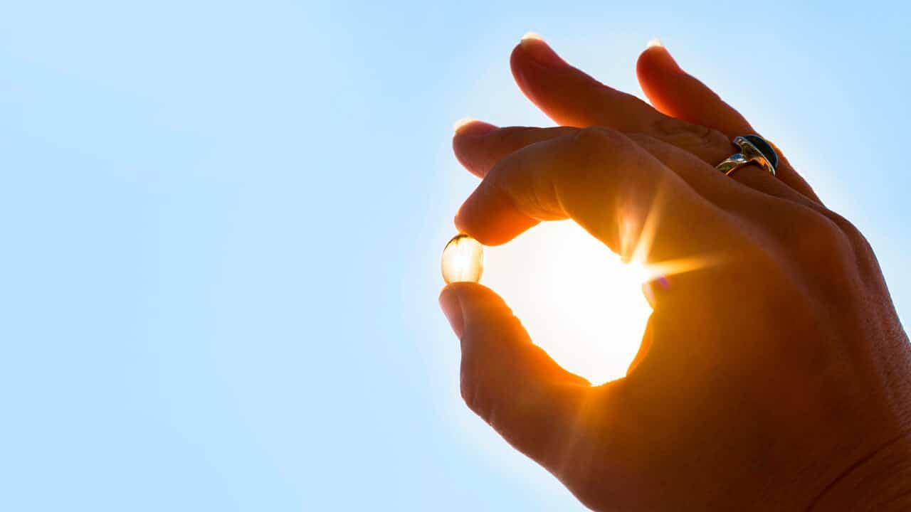 Mão segurando cápsula de vitamina D, virada para o sol