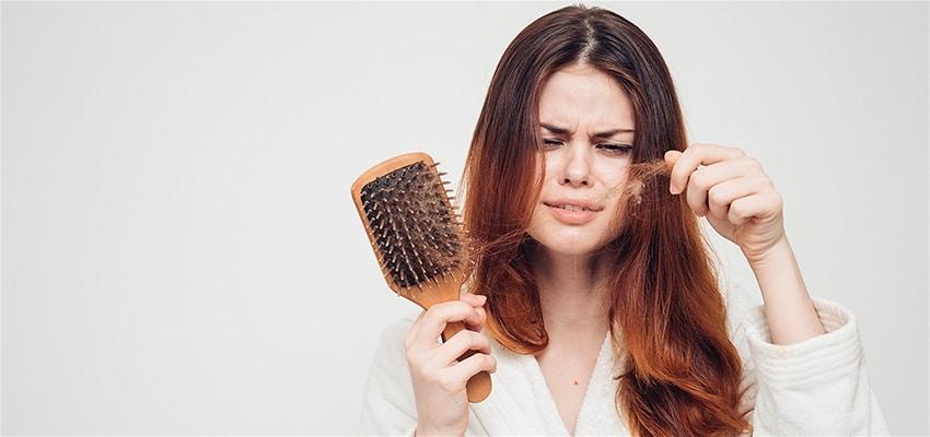 mulher penteando o cabelo com feição de desagrado