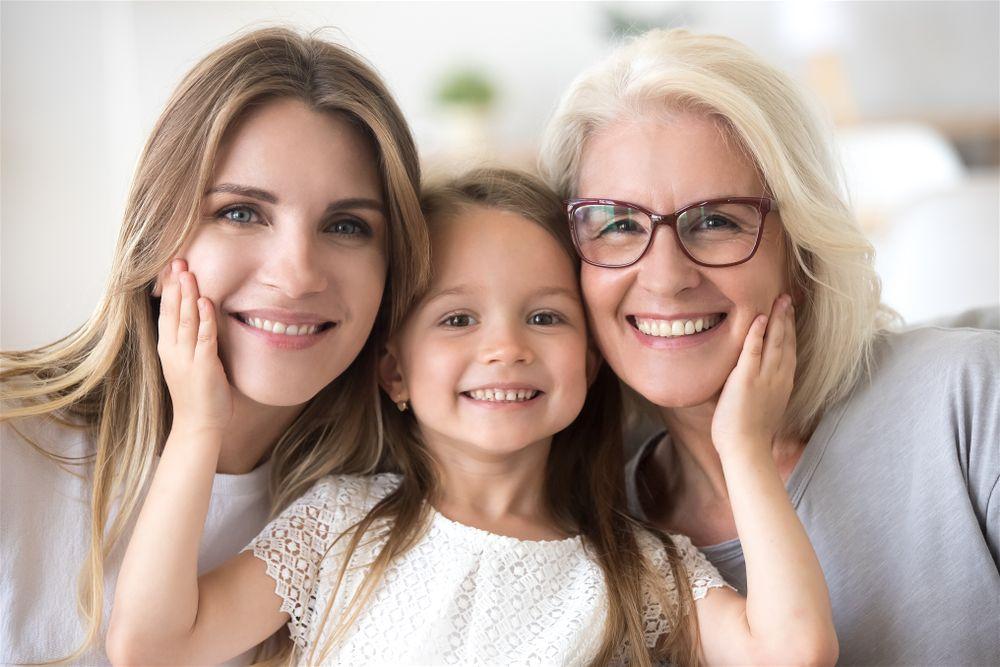 Criança sorrindo com sua mãe e vó