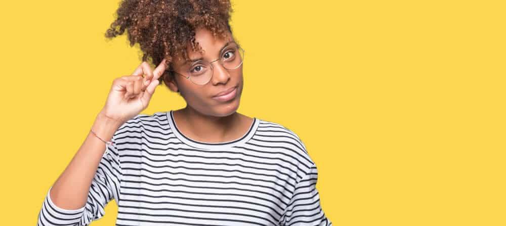 Mulher com blusa listrada e cabelo amarrado apontando para a cabeça