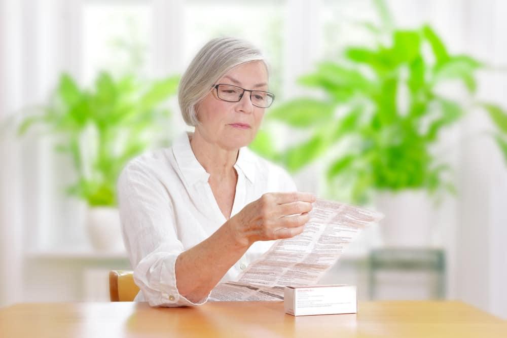 mulher lendo bula de remedio