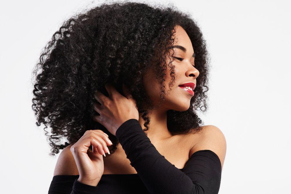 Mulher negra com cabelo cacheado