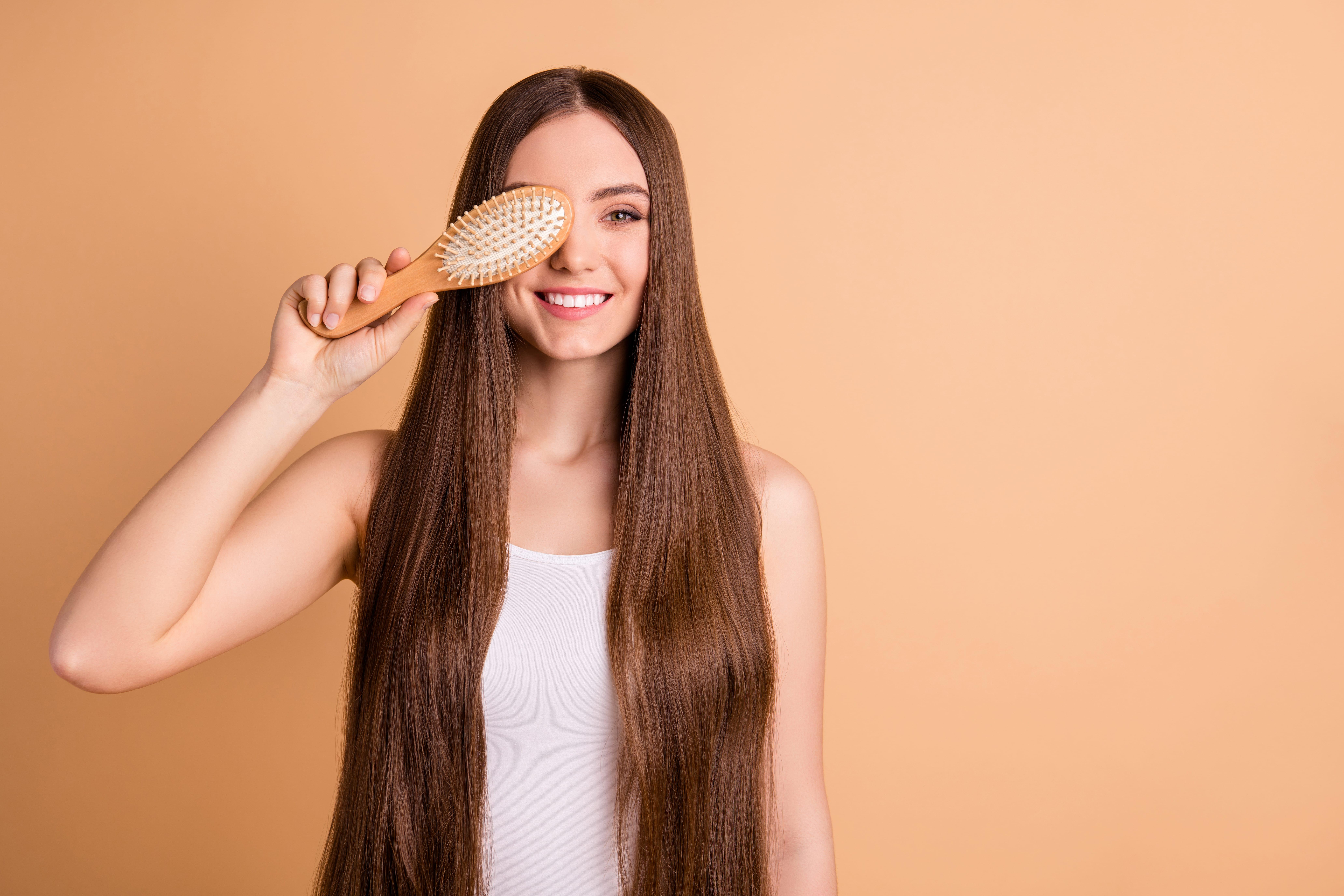 mulher com o cabelo penteado segurando um pente sobre o rosto