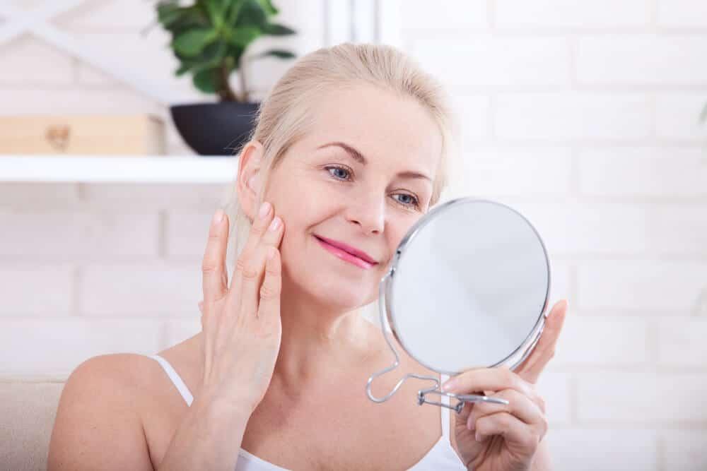 Mulher se olhando no espelho após passar colágeno